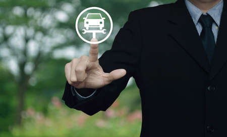 Businessman pressing service fix car with wrench tool flat icon over blur flower and tree in park, Business repair car concept