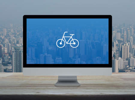 Bicycle flat icon with modern laptop computer on wooden table over office building tower and skyscraper in city, Business bicycle shop online concept