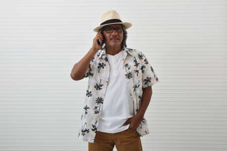 Happy senior traveler asian man wearing straw hat, sunglasses and summer shirt talking on modern smart phone over white wall background, Summer holiday concept