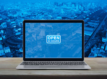 Open 24 hours flat icon with modern laptop computer on wooden table over city tower, street, expressway and skyscraper, Business full time service online concept