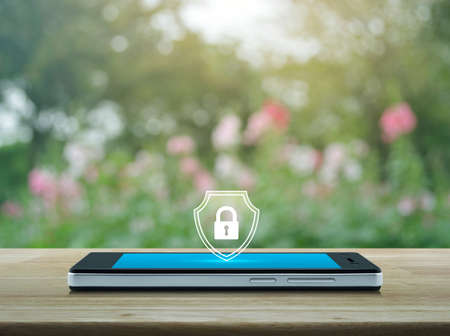 Padlock with shield flat icon on modern smart mobile phone screen on wooden table over blur pink flower and tree in park, Business security insurance online concept