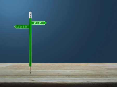 2020 and 2019 direction sign plate with green pencil on wooden table over light blue gradient background, Business happy new year planning concept