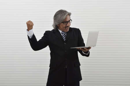 Happy excited elderly asian businessman in black suit and eyeglasses looking at laptop computer and raising his arm up, Business success concept Stockfoto