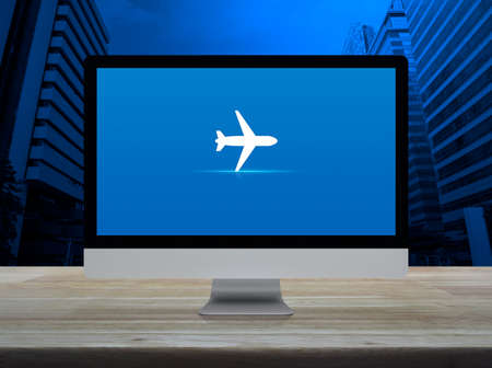 Airplane flat icon on desktop modern computer monitor screen on wooden table over office city tower and skyscraper, Business airplane transportation online concept Stockfoto