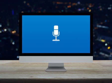 Microphone flat icon on desktop modern computer monitor screen on wooden table over blur colorful night light city tower and skyscraper, Business communication online concept