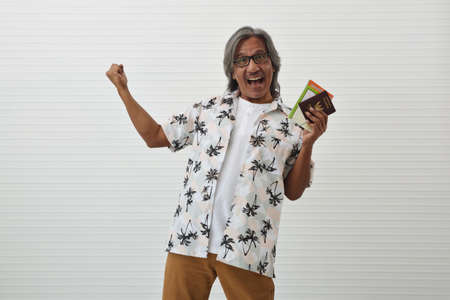 Happy senior traveler asian man wearing glasses and summer shirt holding travel map and Thailand passport, showing his fist standing over white wall background, Business summer holiday concept