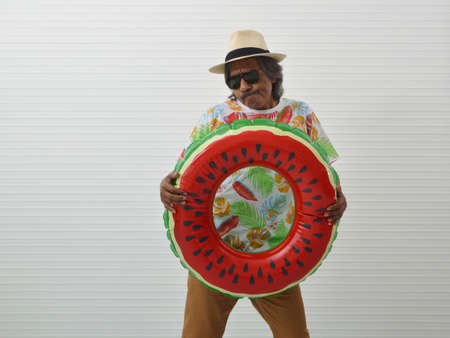 Happy elderly traveler asian man wearing summer shirt, straw hat and sunglasses holding inflatable ring over white wall, Funny face expression, Summer holiday concept