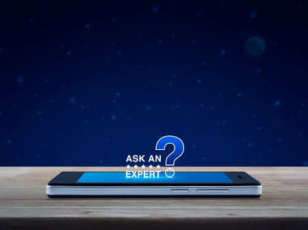 Ask an expert with stars and question mark sign icon on modern smart mobile phone screen on wooden table over fantasy night sky and moon, Business communication online concept