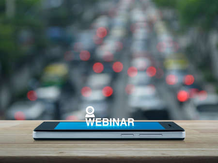Webinar flat icon on modern smart mobile phone screen on wooden table over blur of rush hour with cars and road in city, Business seminar online concept