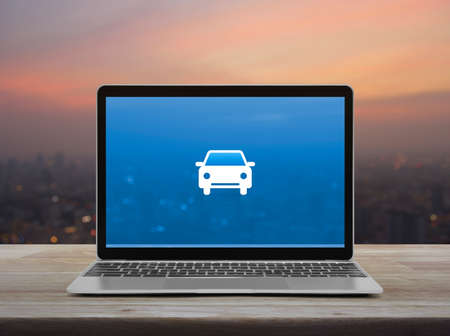 Car flat icon with modern laptop computer on wooden table over blur of cityscape on warm light sundown, Business service taxi car online concept
