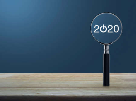 2020 start up flat icon with magnifying glass on wooden table over light blue gradient background, Business happy new year 2020 concept