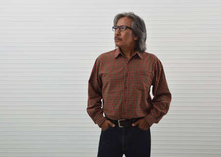 Confident senior man in red casual shirt, blue jeans and eyeglasses standing over white wall background, Business success concept Фото со стока