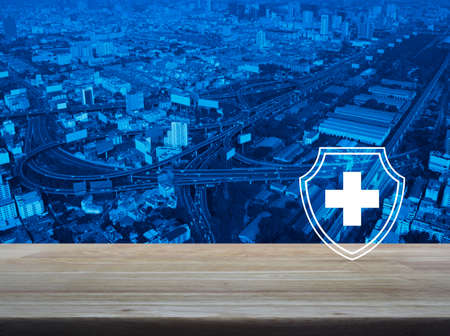 Cross shape with shield flat icon on wooden table over modern city tower, street, expressway and skyscraper, Business healthy and medical care insurance concept