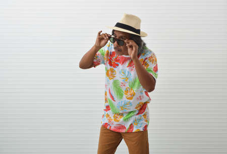Suspicious elderly traveler asian man wearing summer shirt, straw hat and sunglasses taking off glasses and looking to something over white wall, Business summer holiday concept Stock fotó
