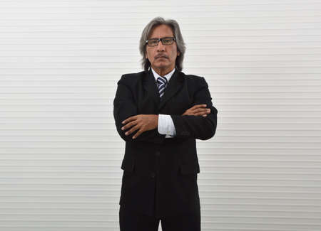Confident elderly asian businessman in black suit and eyeglasses posing with arms crossed and looking at camera, Business success concept Фото со стока