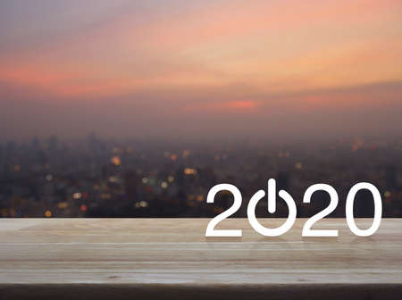 2020 start up business flat icon on wooden table over blur of cityscape on warm light sundown, Happy new year 2020 concept