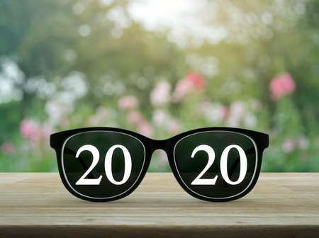 2020 white text with black eye glasses on wooden table over blur pink flower and tree in garden, Business vision happy new year 2020 concept