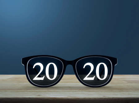2020 white text with black eye glasses on wooden table over light blue gradient background, Business vision happy new year 2020 concept Stock Photo