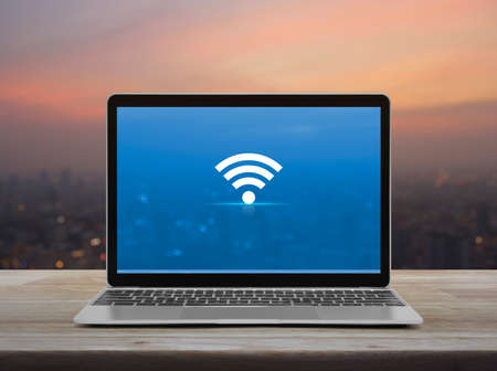 Wi-fi flat icon with modern laptop computer on wooden table over blur of cityscape on warm light sundown, Technology internet online concept