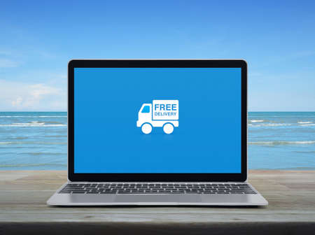 Free delivery truck flat icon with modern laptop computer on wooden table over tropical sea and blue sky with white clouds, Business transportation online concept
