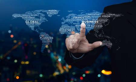 Homme d'affaires appuyant sur la carte du monde des mots d'affaires mondiaux sur la tour de la ville moderne et le gratte-ciel de la veilleuse colorée flou Banque d'images