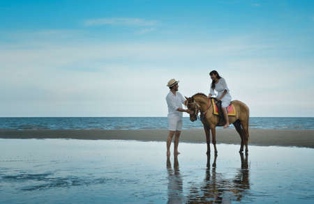 Romantic loving couple with horse on the beach over tropical sea and blue sky, Honeymoon vacation and wedding concept Archivio Fotografico