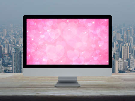 Desktop modern computer monitor with pink love heart screen on wooden table over office building tower and skyscraper in city, Business internet dating online, Valentines day concept
