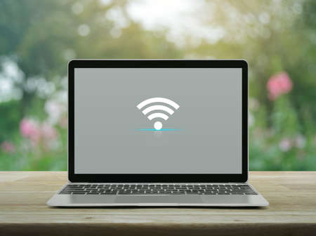 Wifi flat icon with modern laptop computer on wooden table over blur pink flower and tree in garden, Technology internet online concept