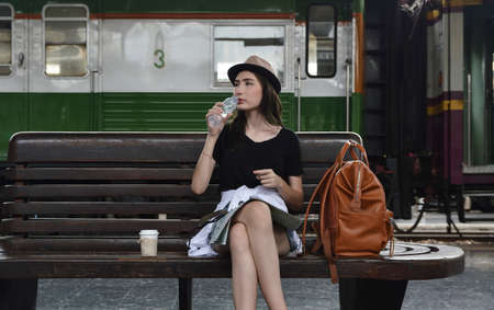 Young beautiful woman traveler drinking water from bottle sitting on wooden old chair with backpack and coffee cup in train station, Business travel holiday relaxation concept