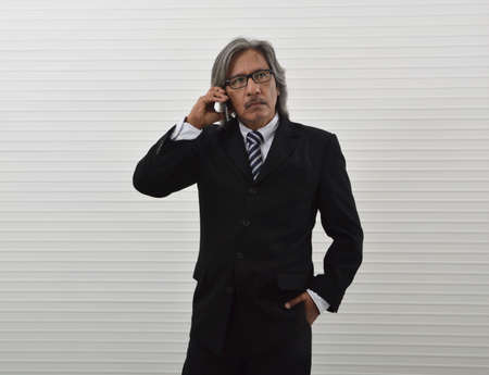 Confident elderly asian businessman in black suit and eyeglasses talking on modern smart mobile phone standing over white wall background, Business communication concept