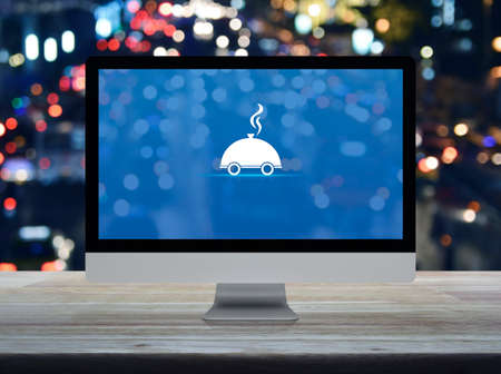 Restaurant cloche flat icon on desktop modern computer monitor screen on wooden table over blur colorful night light traffic jam road in city, Business food delivery online concept
