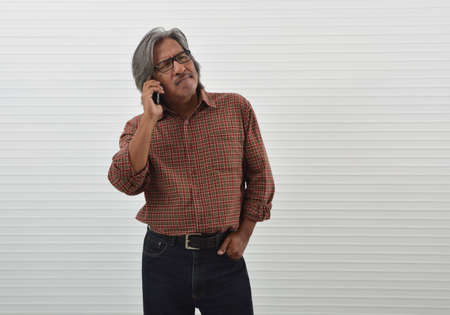 Thoughtful asian senior businessman in red casual shirt, blue jeans and eyeglasses talking on modern smart phone standing over white wall background, Business communication concept 版權商用圖片