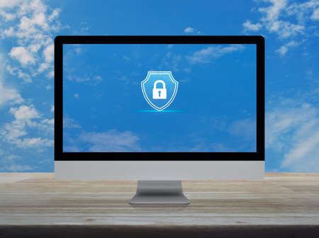 Padlock with shield flat icon on desktop modern computer monitor screen on wooden table over blue sky with white clouds, Business security insurance online concept