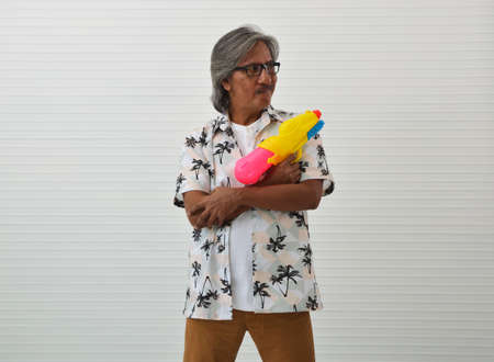 Happy senior traveler asian man wearing glasses, summer shirt and brown shorts holding colorful water gun standing over white wall background, Funny face expression pose, Business summer holiday concept