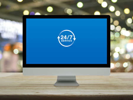 24 hours service flat icon on desktop modern computer monitor screen on wooden table over blur light and shadow of shopping mall, Business full time service online concept Stock Photo