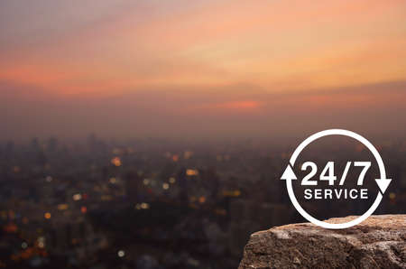 24 hours service flat icon on rock mountain over blur of cityscape on warm light sundown, Business full time service concept