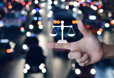 Law flat icon on finger over blur colourful night light city with cars and road, Business legal service concept