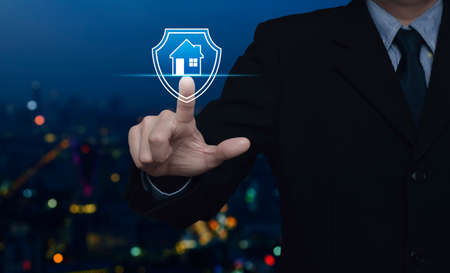 Businessman pressing house with shield flat icon over blur colorful night light modern city tower and skyscraper, Business home insurance and security concept