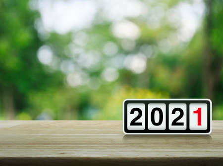 Retro flip clock with 2021 text on wooden table over blur green tree in park, Happy new year 2021 cover concept