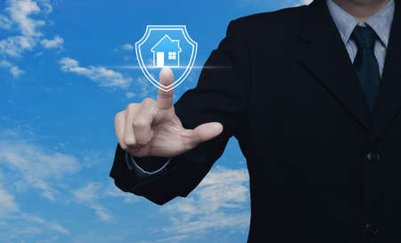 Businessman pressing house with shield flat icon over blue sky with white clouds, Business home insurance and security concept 免版税图像