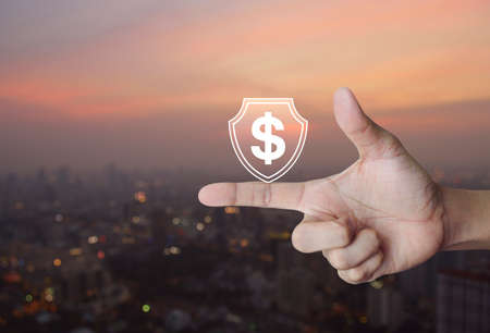 Hand pressing dollar with shield flat icon over blur of cityscape on warm light sundown, Business money insurance and protection concept