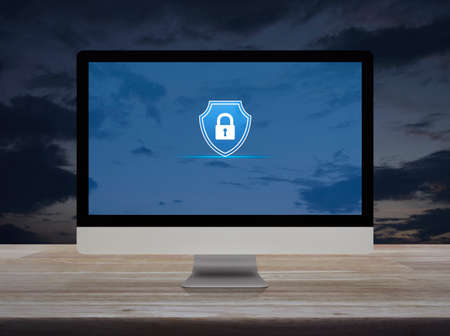 Padlock with shield flat icon on desktop modern computer monitor screen on wooden table over sunset sky, Business security insurance online concept 免版税图像