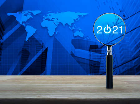 2021 start up flat icon with magnifying glass on wooden table over world map and modern city tower and skyscraper, Business happy new year 2021 cover concept, Elements of this image furnished by NASA
