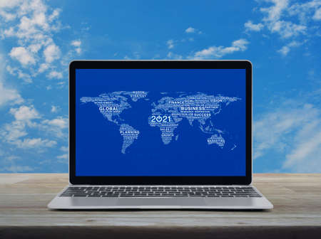 Start up 2021 business icon with global words world map with modern laptop computer on wooden table over blue sky with white clouds. Standard-Bild
