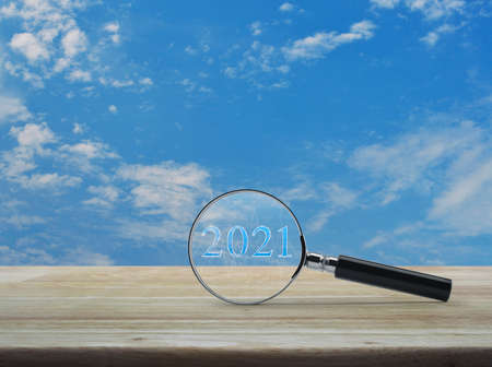 Magnifying glass with 2021 text and financial graph on wooden table over blue sky with white clouds, Business happy new year research cover concept Standard-Bild