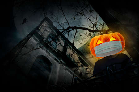 Halloween jack o lantern pumpkin wearing medical face mask standing over grunge castle, dead tree, bird fly, full moon and cloudy spooky sky, Halloween and coronavirus or covid-19 concept