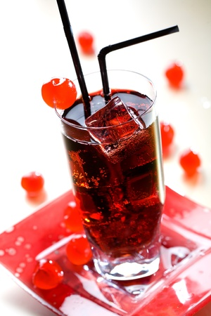 Red drink with ice cubes and black sipper photo