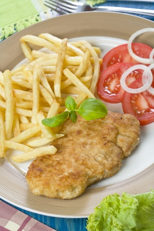 Chicken cutlet with French fries and tomato photo