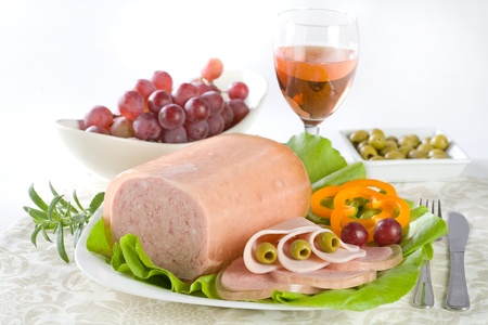 Luncheon meat, salad, olives and grapes Stock Photo
