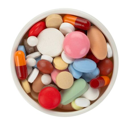 Colored pills in white bowl - top view